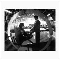 Л.С. Львов (справа) и Э.А. Талныкин смотрят КАМАК-модуль, предназначенный для автоматизации научного эксперимента в составе КАМАК-крейта. Источник: Фотоархив Отделения ГПНТБ СО РАН.